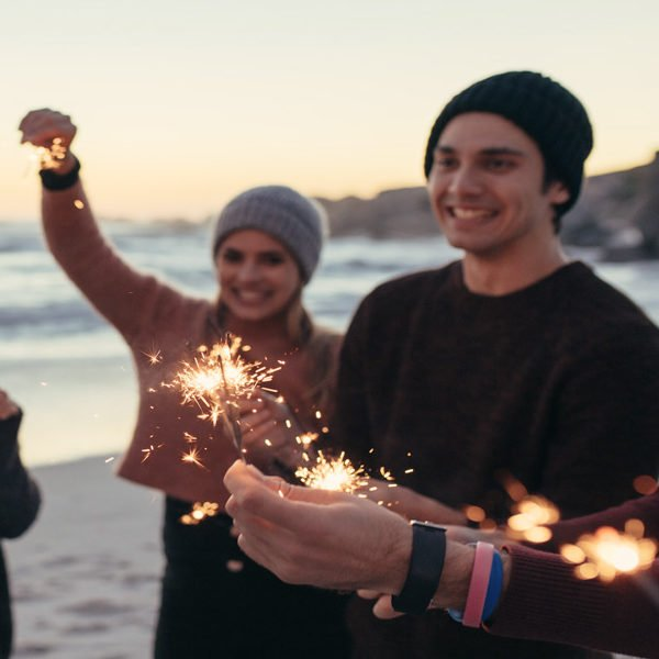 People holding sparklers on the beach