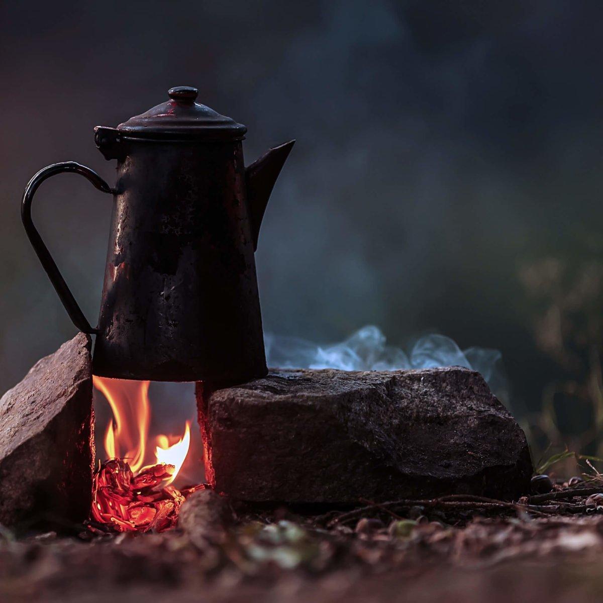 A tea kettle on a camp fire.