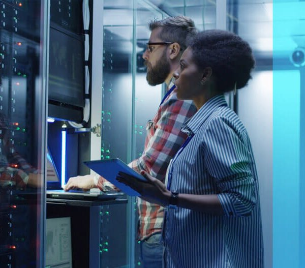 A man and a woman work on a computer server together.