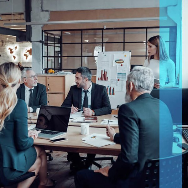A group of marketers work together at a communal table in an office.