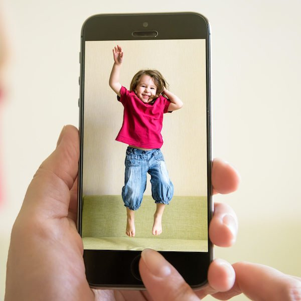 Mother taking photo of jumping baby girl with her mobile phone