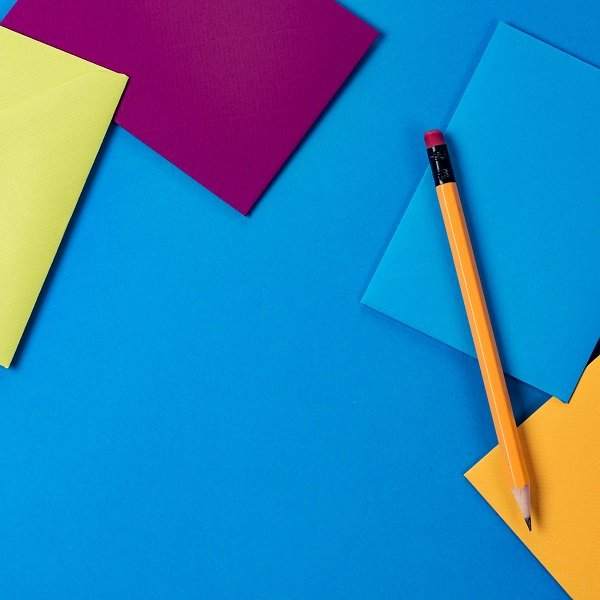 different colored envelopes with a pencil behind a blue background