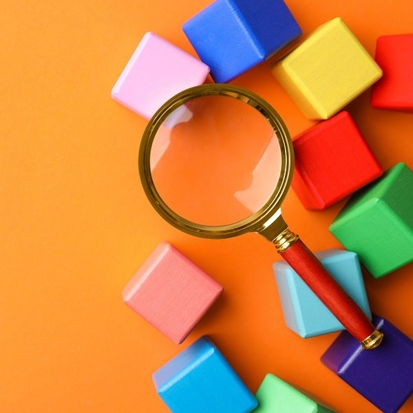 Magnifying glass on an orange background, surrounded by multi-colored blocks. Finding what you need in a Google Product Search.