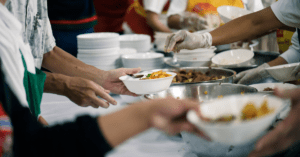 People giving food to others.