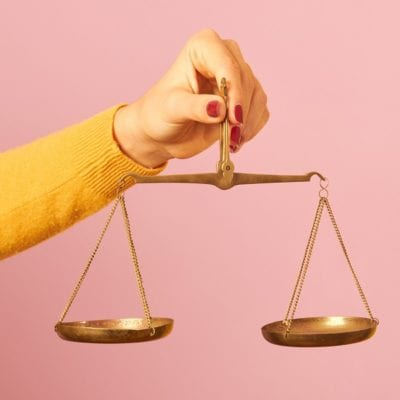 woman hand holding a balance on pink background