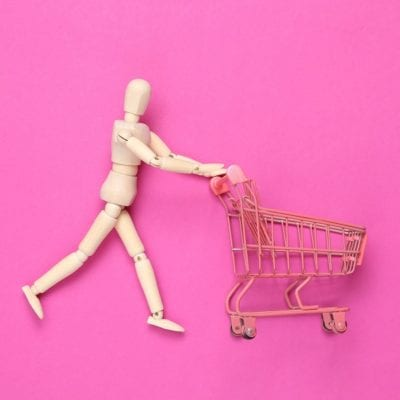 Wooden puppet with Mini shopping cart on pink background