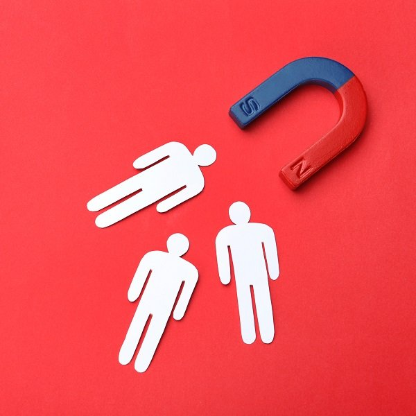 Magnet attracting people traffic on color background, top view with space for text. Marketing concept