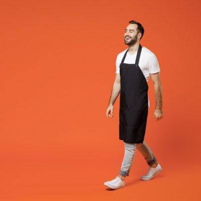 Full length young confident fun man 20s barista bartender barman employee in black apron white t-shirt work in coffee shop walk go isolated on orange background studio. Small business startup concept.